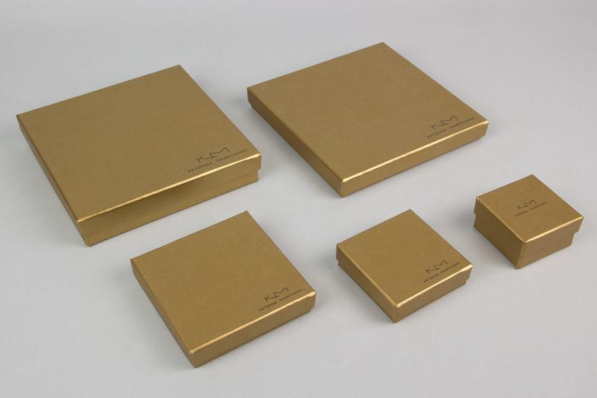 Κουτί κοσμημάτων σε χρυσό χρώμα με τυπωμένο στο καπάκι το λογότυπο της σχεδιάστριας Κατερίνας Μακρυγιάννη.