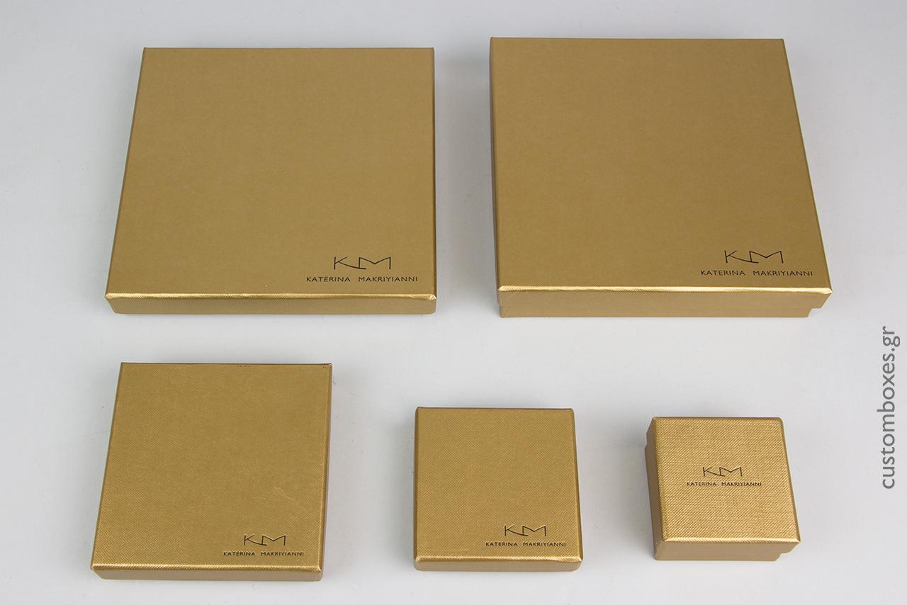 Κουτιά κοσμημάτων σε χρυσό χρώμα με τυπωμένο στο καπάκι το λογότυπο της σχεδιάστριας Κατερίνας Μακρυγιάννη.