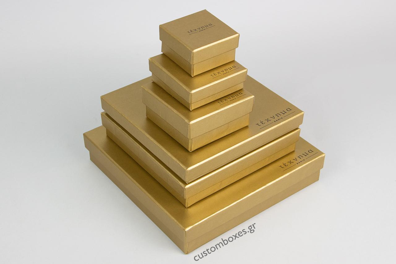 Κουτιά κοσμημάτων σε χρυσό χρώμα με τυπωμένο στο καπάκι το λογότυπο του καταστήματος «Τέχνημα» με έδρα τα Χανιά.