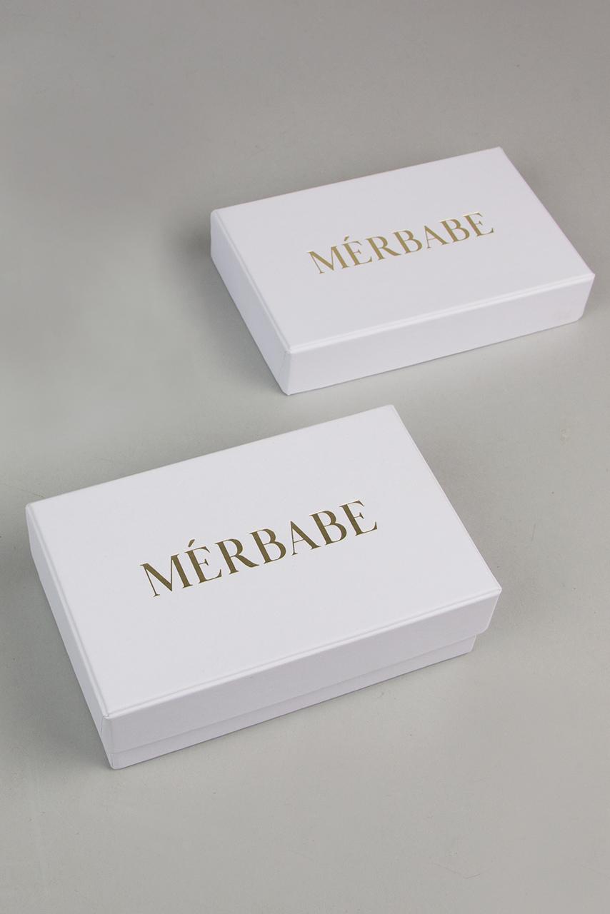 Λευκό κουτί κοσμημάτων MÉRBABE με εκτύπωση του λογότυπου της εταιρείας στο καπάκι (χρυσαφένια απόχρωση).