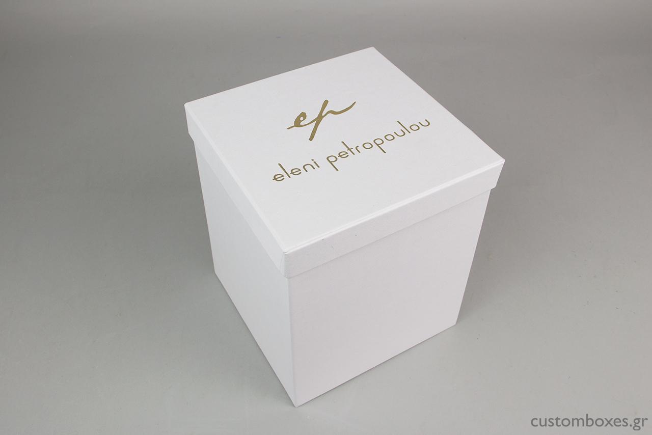 Σκληρό κουτί κοσμημάτων σε λευκό χρώμα με τυπωμένο στο καπάκι το λογότυπο της σχεδιάστριας Ελένης Πετροπούλου.